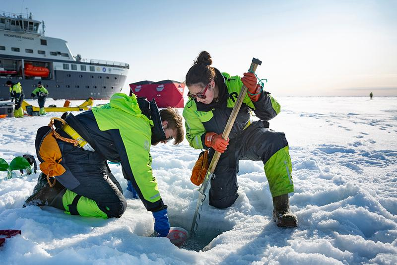 Scientists working on the sea ice. Large research vessel in the background.