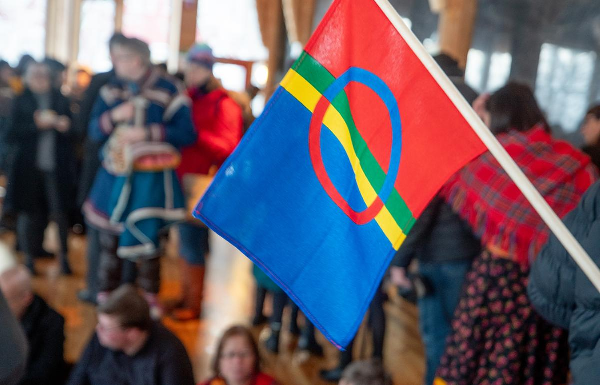 Sami flag and people indoors.