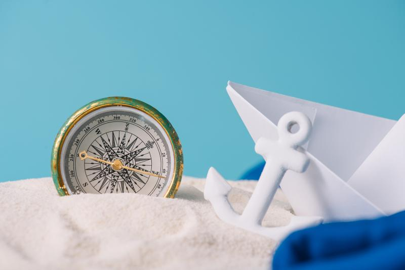 33349755-white-sand-with-paper-boat-anchor-and-compass-isolated.jpg