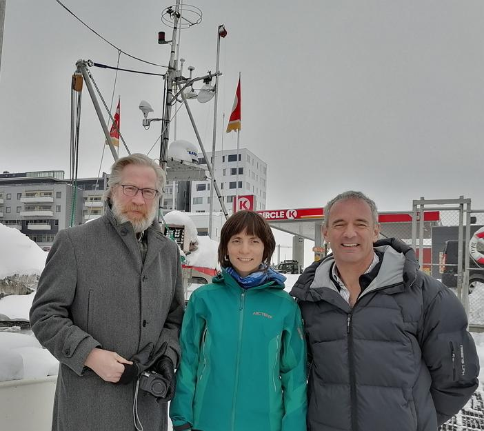 3 people standing infront of a boat in the harbour