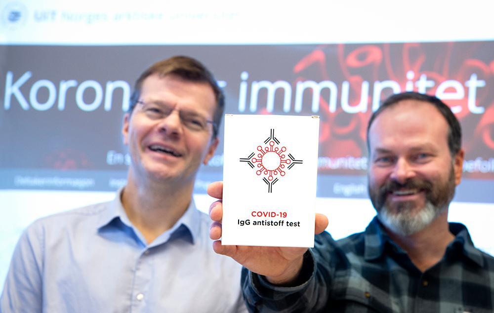 to forskere som smiler og holder en antistoff-test