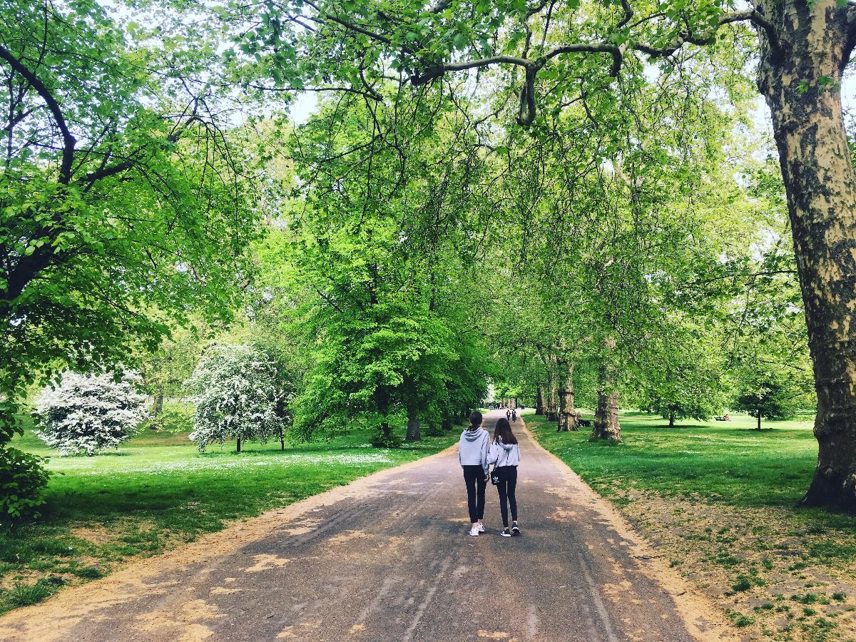to jenter som går gjennom en park