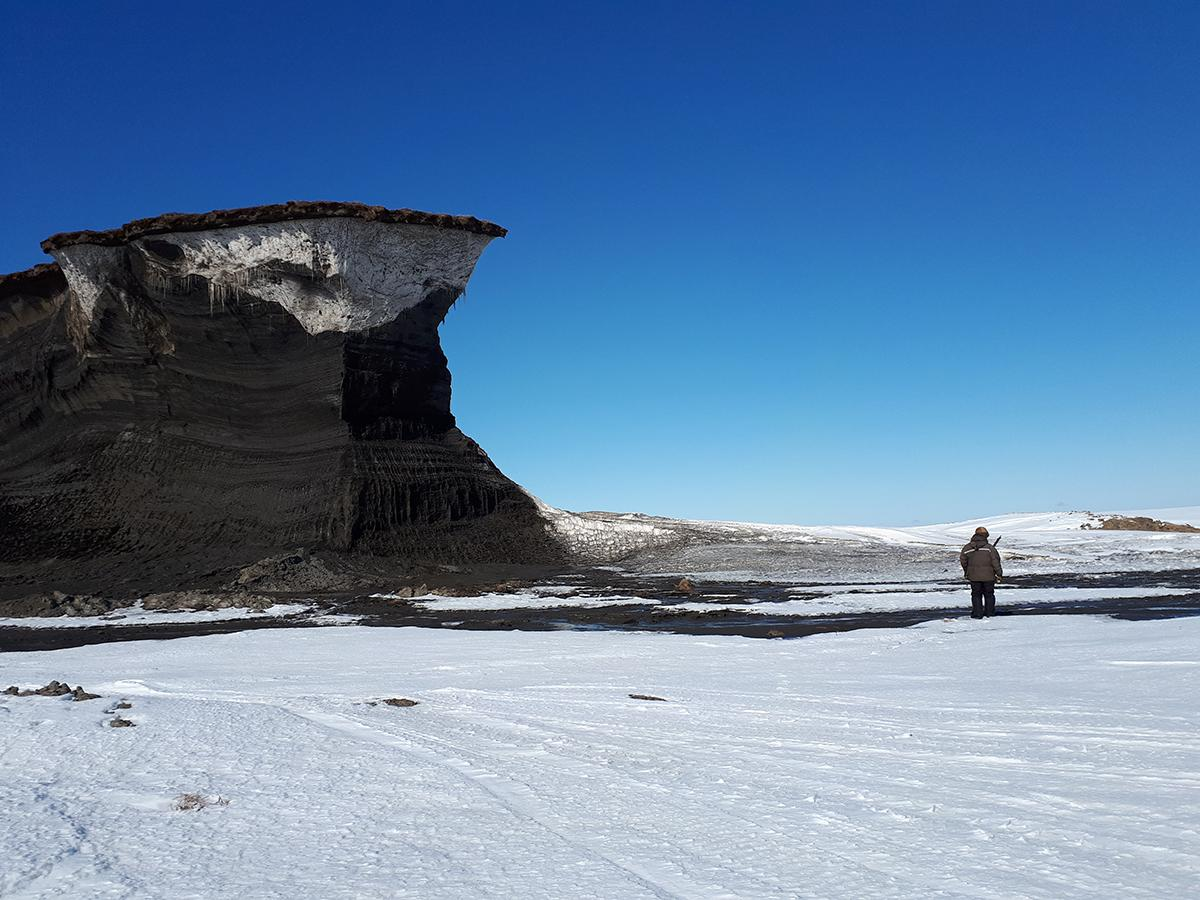 Small man in ice-covered landscape